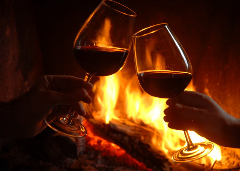 2 glasses of red wine fireplace